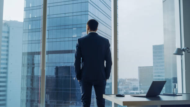 back view of the thoughtful businessman wearing a suit standing in his office, hands in pockets and contemplating next big business deal, looking out of the window. big city business district panoramic window view. - executivo imagens e fotografias de stock