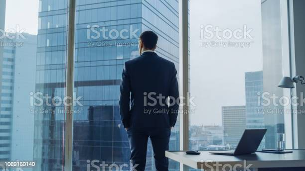 Back View Of The Thoughtful Businessman Wearing A Suit Standing In His Office Hands In Pockets And Contemplating Next Big Business Deal Looking Out Of The Window Big City Business District Panoramic Window View Stock Photo - Download Image Now