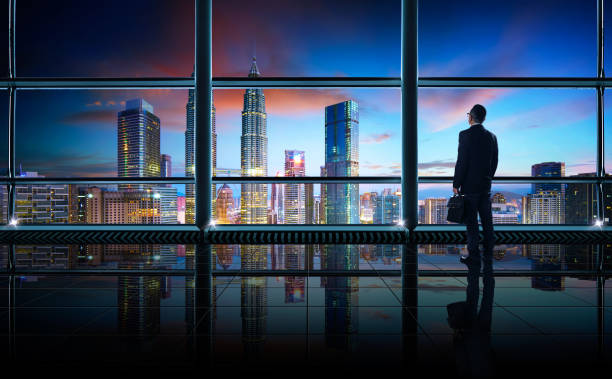 Back view of thoughtful businessman looking out of big office window at office Back view of thoughtful businessman looking through window at big modern city,planning future project concept, early morning scene . millionnaire stock pictures, royalty-free photos & images