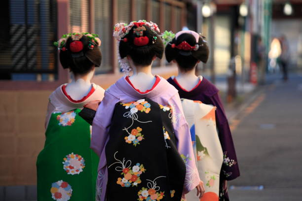 Back view of three geishas Hanamikoji, Kyoto City, Japan - Oct 6, 2010: The backview of three geishas, who were going for their appointment at dusk in Kyoto, Japan. geisha stock pictures, royalty-free photos & images