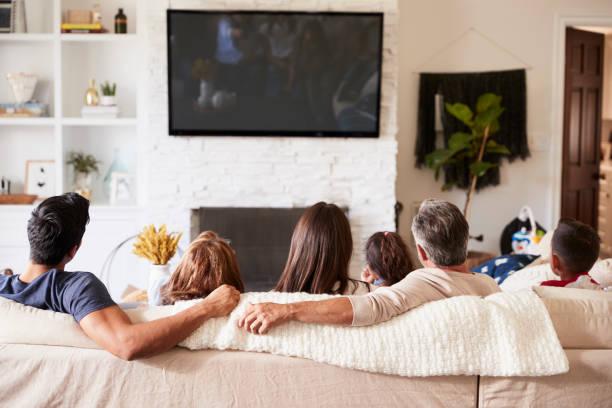 baksidan på tre generation spansktalande familj sitter på soffan tittar på tv - konstkultur och underhållning bildbanksfoton och bilder