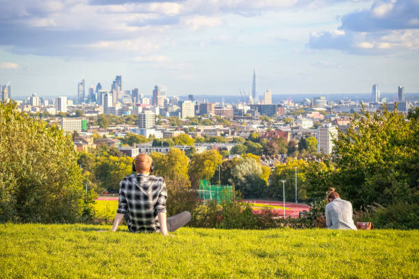 Back view of tourists looking over London city skyline from Hampstead Heath in London stock photo