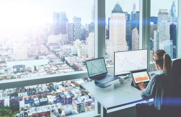 Back view of trader manager sitting at panoramic skyscraper office desktop front PC computer with financial graphs and statistics on screen. Analysis of digital market and investment in block chain stock photo