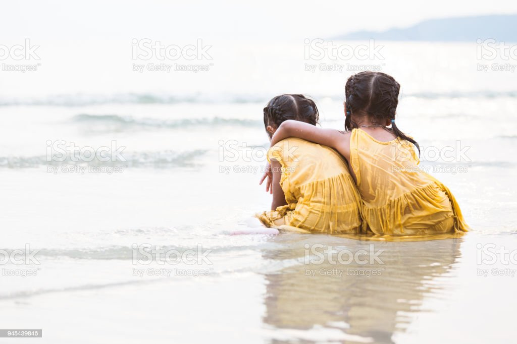 Back view of two cute asian little child girls hugging and having fun to play on beach together stock photo