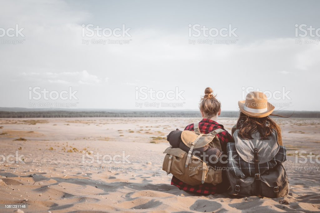 Back view of two female friends sitting on the desert Outdoor shot of two young women sitting on the dune, holding backpacks. Back view. Adolescence Stock Photo