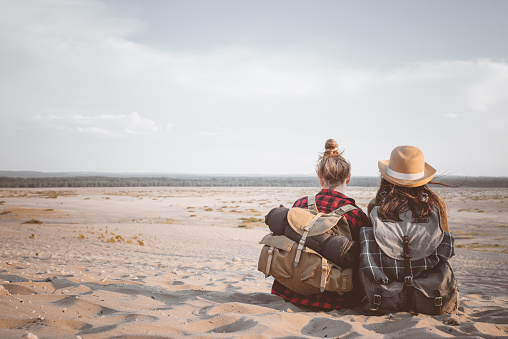 Back View Of Two Female Friends Sitting On The Desert Stock Photo - Download Image Now