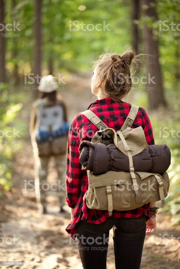 Back view of two hipster girls walking in the forest Outdoor shot of two young women walking in the forest, holding backpacks. Adolescence Stock Photo