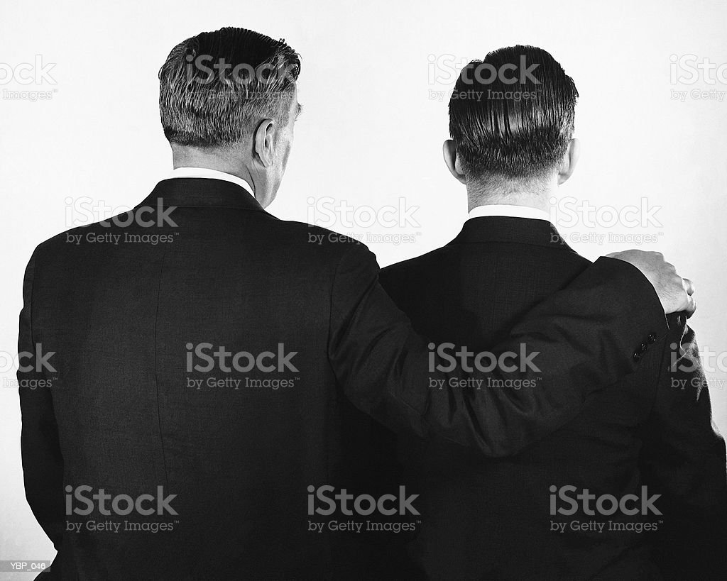 Back view of two men, one with arm around other royalty-free stock photo
