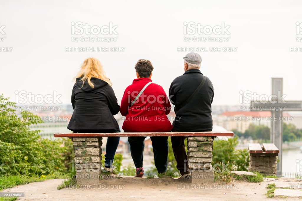 Back view of two woman and one older man sitting on a bench looking at the city Budapest from above. stock photo