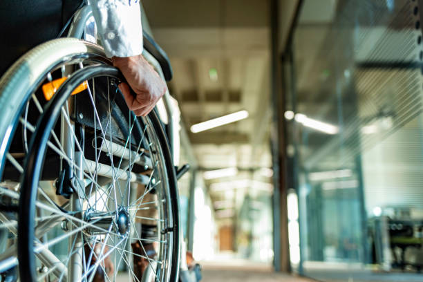 Back view of unrecognizable person in a wheelchair in a hallway Close-up Of one unrecognizable Businessman Sitting On Wheelchair In Office during the day. paraplegic stock pictures, royalty-free photos & images