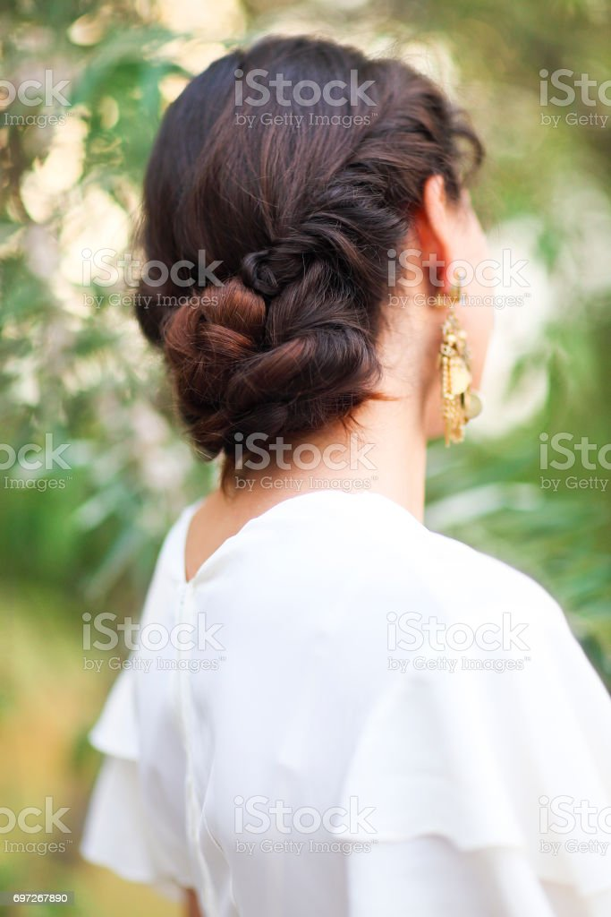 Back view of unrecognizable young woman with brunette hair in white wedding dress and vintage gold jewelry earrings stock photo