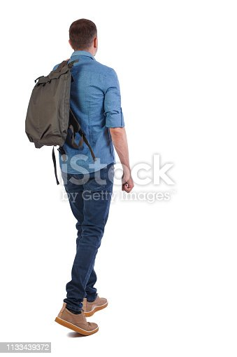 istock back view of walking  man  with green bag. 1133439372
