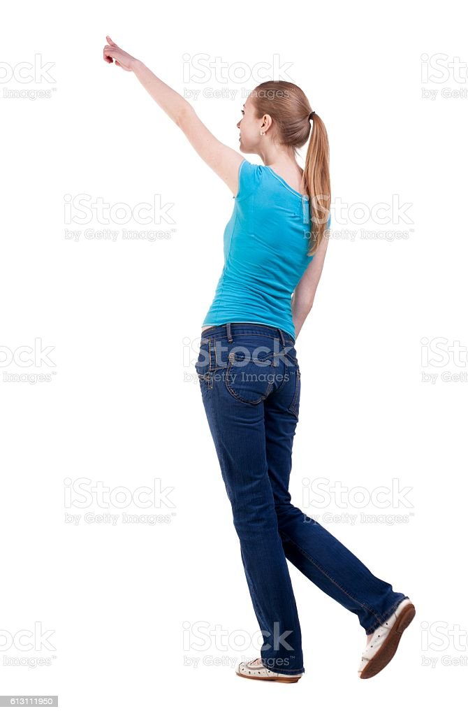a317ed9438fc back view of walking woman in jeans and shirt pointing foto stock royalty -free