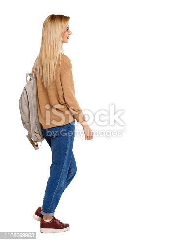 istock back view of walking  woman  with backpack. 1128069963