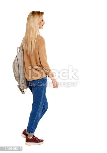istock back view of walking  woman  with backpack. 1129645315