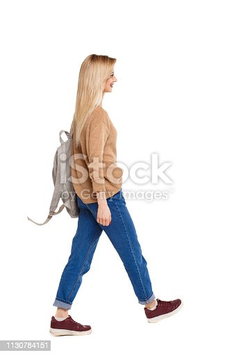 istock back view of walking  woman  with backpack. 1130784151