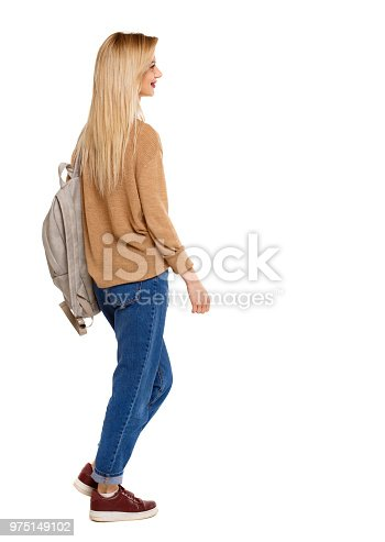 istock back view of walking  woman  with backpack. 975149102