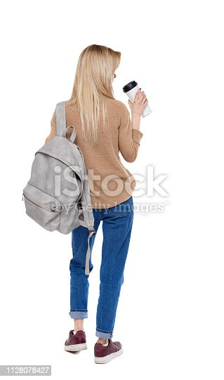 istock Back view of walking  woman  with coffee cup and backpack. 1128078427