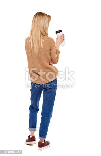 istock Back view of walking  woman  with coffee cup and backpack. 1128087082