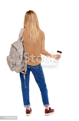 istock Back view of walking  woman  with coffee cup and backpack. 1129832603