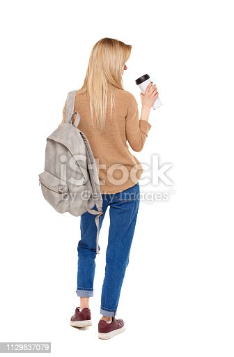 istock Back view of walking  woman  with coffee cup and backpack. 1129837079