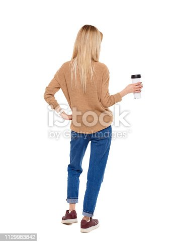 istock Back view of walking  woman  with coffee cup and backpack. 1129983842