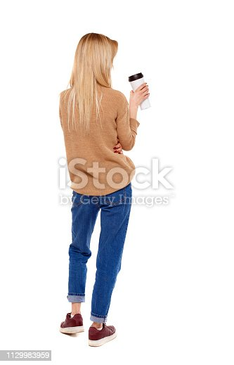istock Back view of walking  woman  with coffee cup and backpack. 1129983959