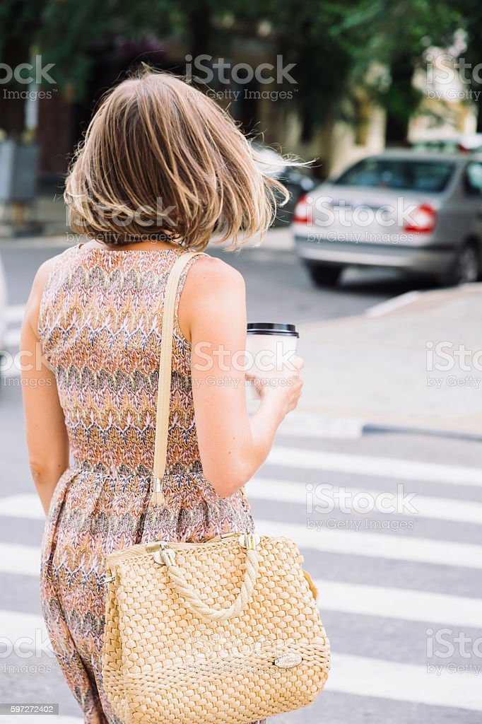 Back view of walking woman with drink Lizenzfreies stock-foto