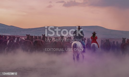 Kayseri/Turkey-October 27 2019: Back view of western cowboy and cowgirl riding horses in dusts in the evening