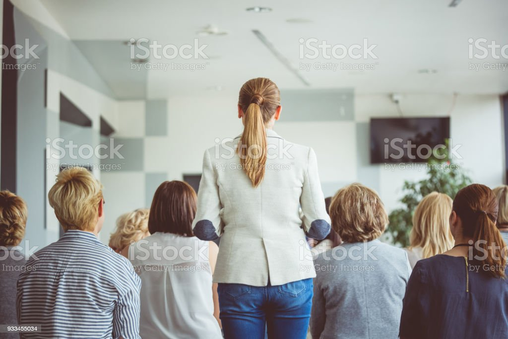 Back view of woman asking question during seminar Back view of woman asking question during seminar. Adult Stock Photo