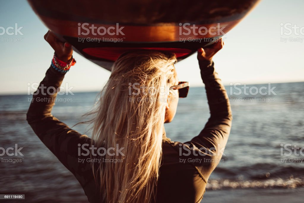 Back view of woman holding surfboard stock photo