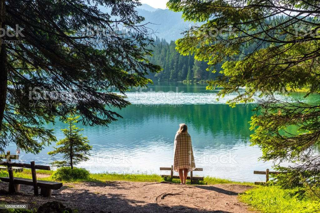 back view of woman in blanket looking at beautiful glacial Black Lake...