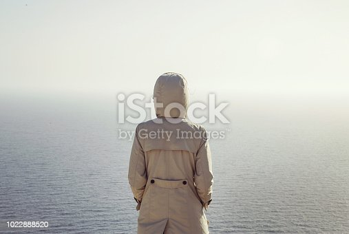 Back view of woman in a trench coat with a hoodie on looking at the ocean, thinking alone concept, self-time concept,