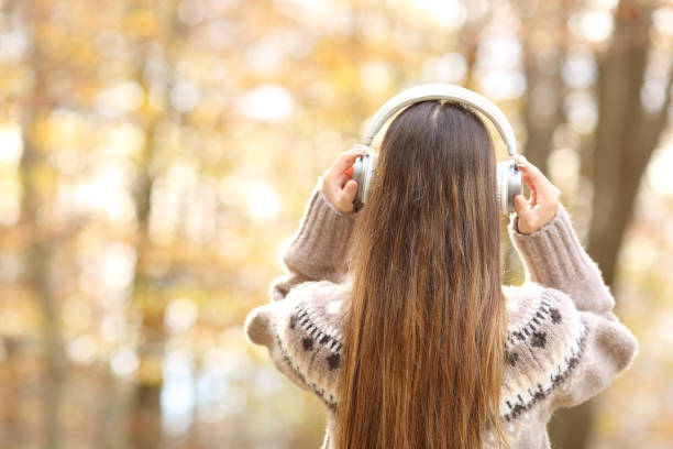 Back view of woman putting headphones in autumn stock photo