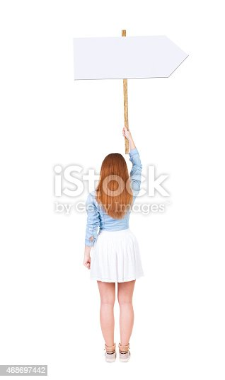 istock Back view  of woman showing a sign board. 468697442