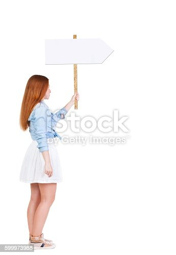 istock Back view  of woman showing a sign board. 599973988