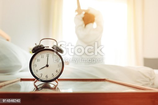 Back view of woman stretching in morning after waking up on bed near window with alarm clock. Holiday and Relax concept. Lazy day and Working day concept. Office woman and worker in daily life theme