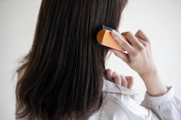 Back view of woman unraveling her hair with a brush stock photo