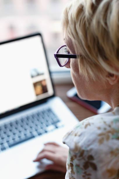 back view of woman using laptop - vertical - fotografias e filmes do acervo