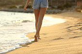 Back view of woman waxed legs walking on the sand