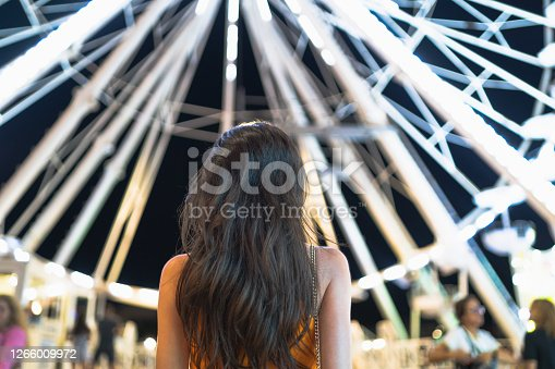Happy brunette woman having fun at amusement park. Relaxing during holidays