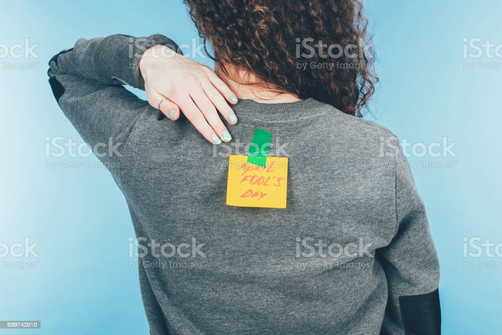 back view of woman with note on sticky tape with april fools day lettering on back, april fools day concept stock photo