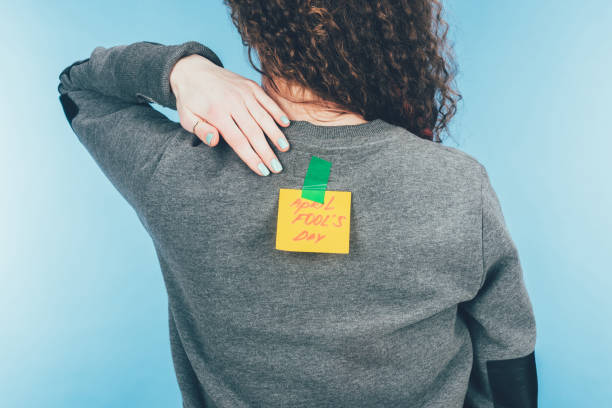 back view of woman with note on sticky tape with april fools day lettering on back, april fools day concept - april fools stock photos and pictures