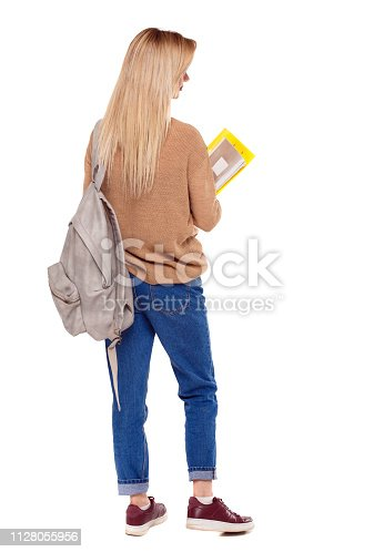 istock Back view of woman  with notebooks and backpack. 1128055956