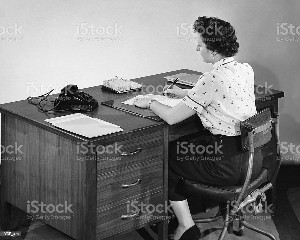 Back view of woman writing and looking at phone royalty-free stock photo