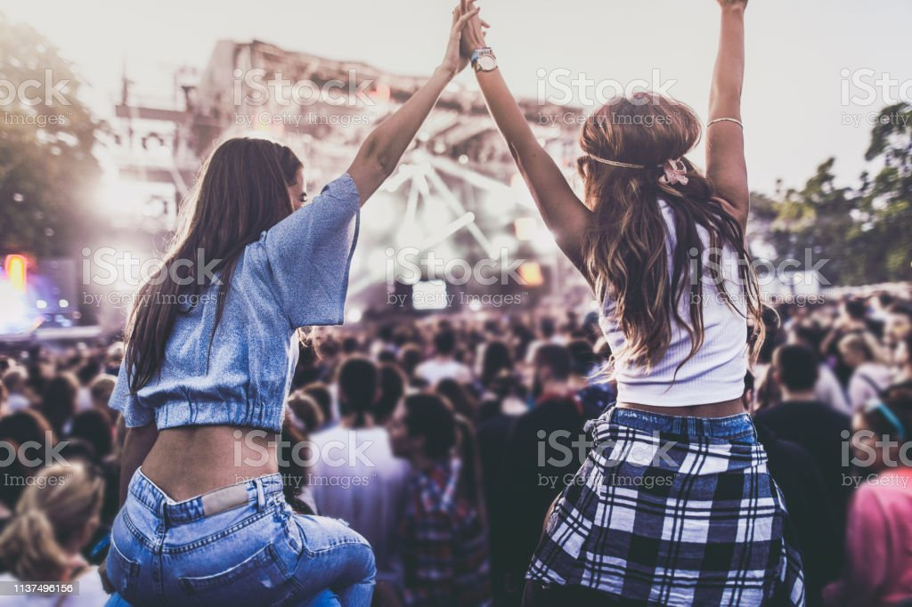 Rear view of carefree women holding hands and having fun on a music...