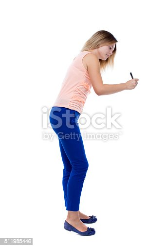 back view of writing beautiful woman. Rear view people collection.  backside view of person. Isolated over white background. Blonde in blue trousers draws a pen in front of him.