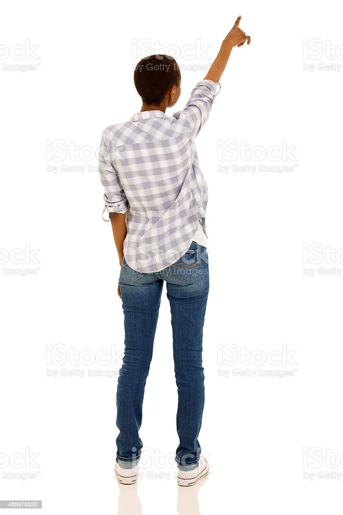 back view of young african woman pointing at empty space stock photo