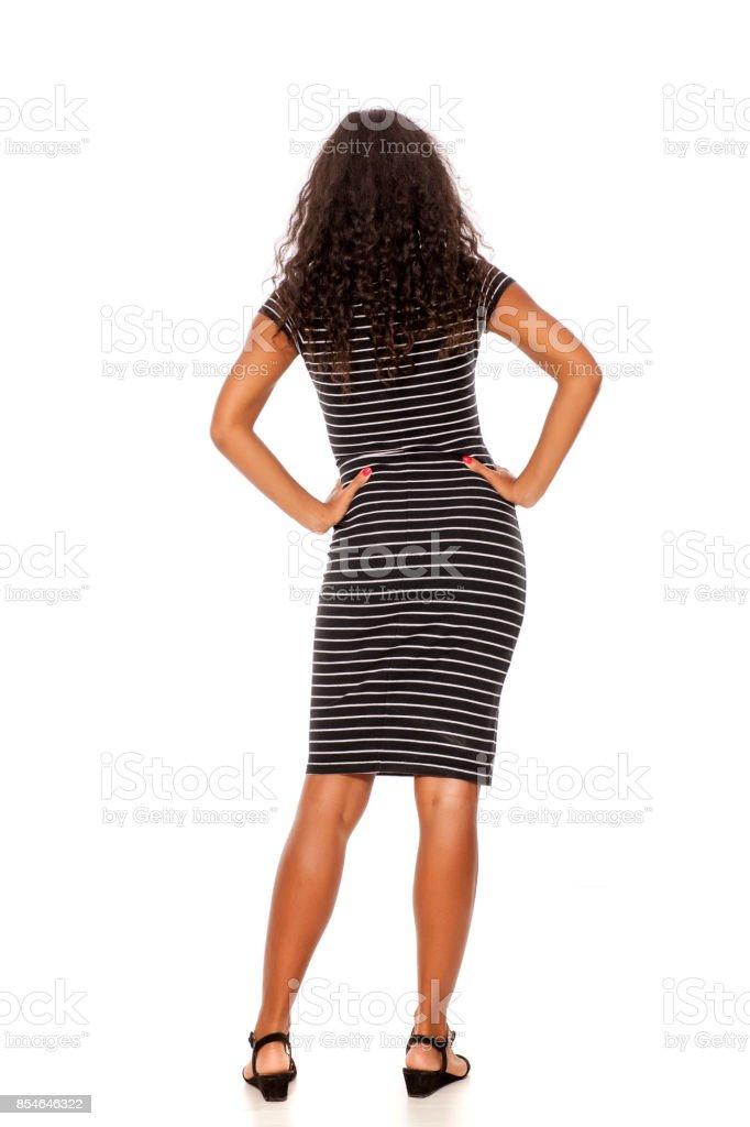 Vue arrière du jeune et assez sombre femme dénudée posant sur fond blanc - Photo