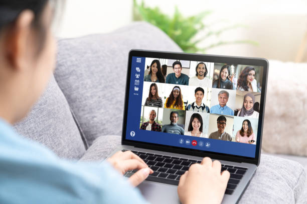 Back view of young asian business woman work remotely at home video conference remote call to corporate group. Meeting online,videocall, group discuss online concept with screen of teamwork on laptop. stock photo